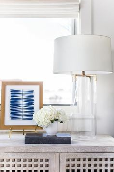 Serena & Lily Brookline Table Lamp sits on a gray wash nightstand with carved check doors displaying lovely flower arrangements in a glass lamp with brass trim.