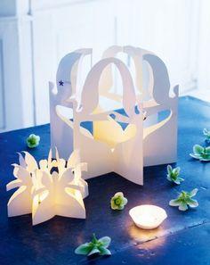 Farandoles d'anges de papier pliés puis découpés qui forment des photophores blancs