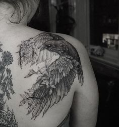 blackwork raven and plant tattoo idea on the shoulder