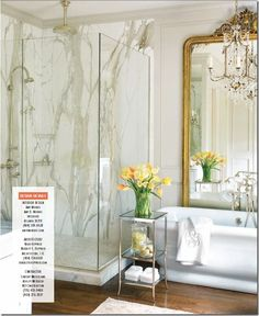 Love the tall mirror, chandelier and the glass shower with marble. Beautiful!