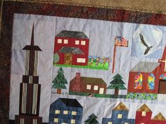 Art Quilt - Building Quilt for Christopher - close up of Skyscraper.I used black and white clip art images of skyscrapers to get ideas of proportions and where to place the light and dark fabrics.  A small stripe gives the visual effect of long windows.  The top spire wa paper pieced.  I make Prairie Points to look like dimensional bushes and flowe beds. (they flap)  Debbie Lange Quilting