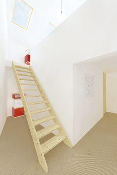 Houten open trap beidt toegang tot open zolder verdieping met logeerkamer. De vloer is voorzien van sisal en de wanden zijn wit gestuct. Ontworpen door De Nieuwe Context