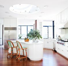 White kitchen with rustic stools and skylight