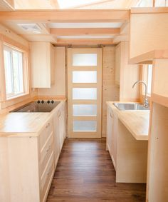 The galley kitchen features soft close drawers and cupboards, an electric cooktop, stainless steel sink, and room for an under-counter refrigerator.