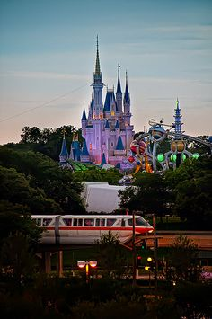 Cinderella's Castle stands tall beyond Tomorrowland and a Monorail train at Walt Disney World shortly before sunset.