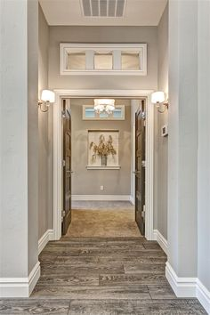 Master Suite Entry with transom windows above and chrome sconces. Crystal Emtek door hardware.