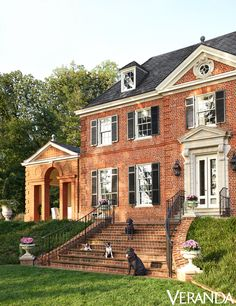 The owner of the house's dogs on the front steps of the Virginia house, built circa 1930. Interior design by Suzanne Kasler, architecture by Madison Spencer.   - Veranda.com