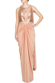 Featuring a rose gold pre draped jersey saree gown with faux metal embellished bodice and detailed bateau neckline, waistline. It has a sheer detailed zipped back by AMIT AGGARWAL Shop now-www.carmaonlineshop.com