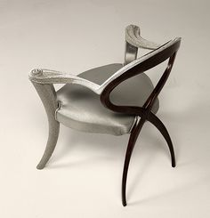 Unique sculptural chair made from sculpted solid walnut with arms and front legs adorned with special pearl finish like caviar. Upholstered in silver pearl fabric.