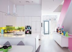 GREAT ROOM: DESIGNER KARIM RASHID'S HELL'S KITCHEN HOME   The pendants overhead, by AXO, are Rashid's design.  The white kitchen features a green-glass backsplash.  The dining table and chairs are Rashid's design for BoConcept.  The console displays ceramic objects from Rashid, Fornasetti, and Ettore Sottsass.