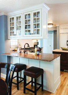 disguise a supporting wall protrusion with a kitchen peninsula + bar seating. The suspending wall units split the kitchen area from the dining space