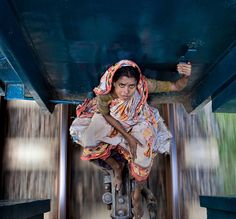 A woman is riding between the railway carriages of a local train heading north from Dhaka, the capital of Bangladesh. It is the month of Ramadan, tens of thousands of people leave the city to go to their home village and celebrate with their families. Trains are packed and many who fail to get tickets before they sell out or can't afford buying them at the black market ride on the roof of the train or, like this woman, finds a quiet spot between the carriages. Photo by Amy Helene Johansson.
