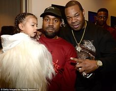 Daddy's girl: Kanye West cuddled up to daughter North and rapper Busta Rhymes after his New York Fashion Week event at Madison Square Garden on Thursday