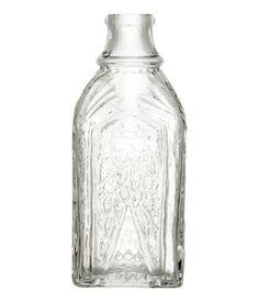 Een glazen fles met een reliëfdessin. Hoogte 18 cm, diameter aan de bovenkant 3 cm.