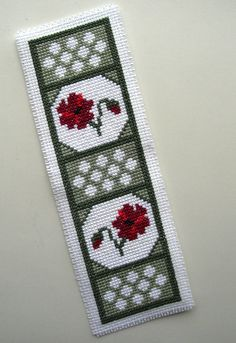 A cross stitched poppy bookmark. Bookmark measures approximately 7 inches long by 2.25 inches wide. The bookmark is backed with felt.