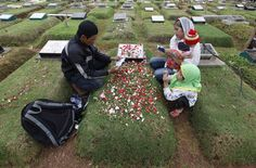 A family reads verses from the Koran at a relative's grave in a cemetery, a day before the Islamic holy month of Ramadan, in Jakarta, on July 9, 2013. Traditionally Indonesian Muslims will visit the graves of their relatives before and towards the end of the the holy month. (Reuters/Enny Nuraheni)