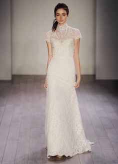 Ivory / Blush re-embroidered lace fit n flare bridal gown with shimmer throughout. Strapless sweetheart neckline with a sheer back bodice. Shown with a sheer beaded and embroidered high neck jeweled fringed jacket.