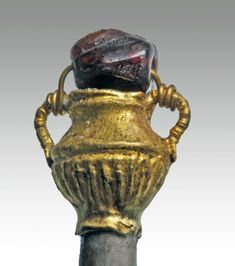 """4Rome, ca. 1st - 4th century CE. Delicate gold amphora mounted on the end of an ivory hair pin (modern) with a purple gemstone suspended above the amphora. Ribbing along base of amphora. 4-7/8""""L.   Provenance: Ex-Private Boulder, CO Collection."""