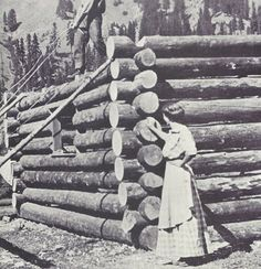 Pioneer woman overseeing the building of her log cabin.