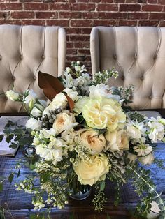 Beautiful late summer wedding with cream and white roses, mixed greenery including magnolia leaves.