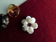 Compoziția florală este confecționată din sidef și mărgele de granat