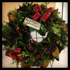 Christmas wreath with fresh evergreens, magnolia leaves, boxwood, holly, and pine cones. By Elly Dickie at the Shamrock Flowers and Gifts.