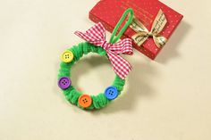 Make an adorable Christmas decoration using pipe cleaner, ribbon and buttons. It makes a great ornament, gift topper or door …