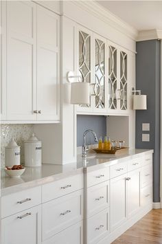 White cabinets, marble mosaic, mullions on upper glass fronted cabinets.