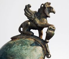 """A griffin (also spelled gryphon and griffon) is a mythical creature. Bulfinch's Mythology describes the griffin as having """"the body of a lion, the head and wings of an eagle, and back covered with feathers."""" The combination of eagle and lion makes the griffin a powerful symbol of vigilance and strength. The bronze griffin in this photo is a crest on a Roman helmet from the first or early second century AD."""
