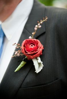 Red, ranunculus and wildflower boutonniere for groomsmen
