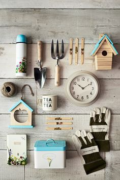 Sainsbury's Autumn/Winter 2015: Outdoor/indoor: Rustic chic home and garden décor – White wall hanging clock, wooden bird house, sky blue colour scheme, cup of tea, green hands gloves, storage tin, roped string, floral drinking flask, mini silver spade and garden fork and woodland notebook. #CamronLatestWork