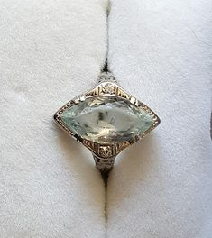 Beautiful antique ring - faceted aquamarine marquise shaped stone set in an 18k white gold filigree setting with two small diamonds on the side. The ring is a size 5 1/2. The stone measures approximately 8mm by 15mm. The stone shows some surface wear.