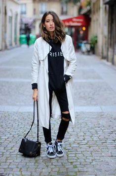 black and white outfit idea - slouchy white coat, ripped black skinny jeans, graphic sweatshirt, and sneakers