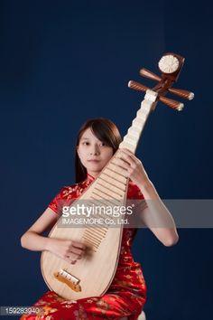 Stock-Foto : Young woman wearing cheongsam and playing pipa