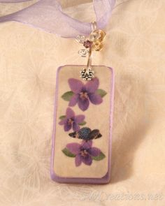 Gorgeous handcrafted painted art domino 'Fleuri' flower domino pendants. This 2x1 inch pendant is a signed purple glitter painted domino with a purple pansy and blue butterfly photograph picture. The