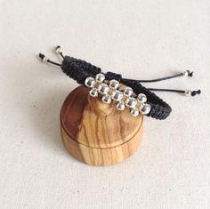Pulsera de macramé hecha con cordón de algodón en color negro y abalorios metálicos en color plata, medida ajustable ya que tiene cierre corredero. La cajita de madera es atrezzo no va con la pulsera. Esta pulsera lleva una bolsa de organza que puede variar en el color. Perfecta para una regalo handmade. _________________________________________________________________________________ Diseñado y hecho a mano en Euskadi con todo el amor que puede dedicarse al hacer una pieza única y exclus...