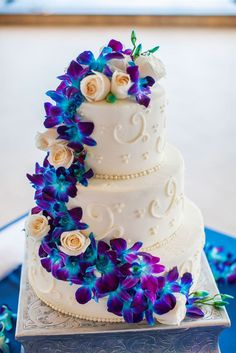 This is a gorgeous beach wedding cake with blue orchids and ivory roses cascading down the side.