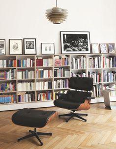 """Dans le salon, Silke a fait installer une bibliothèque en contreplaqué de hêtre (Moebel Horzon) à la façon d'un soubassement, contre un mur de 3,60 m de haut. Dessus, elle a posé des dessins et photos en noir et blanc. De gauche à droite, dessin Rabbit de Bettina Krieg, photo de Gunnar Porykis, photos Fulgurator Action de Julius von Bismarck et trois collages intitulés A Sentimental Journey through my Mind de Marcel Brühler. Devant, fauteuil """"Lounge Chair"""" de Charles & Ray Eames, Vitra. Au…"""
