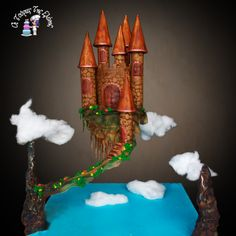 Castle Gravity Cake!!! Everything is edible !! Cake is the castle and all the decorations are sugarpaste.Clouds are made from cotton candy!!