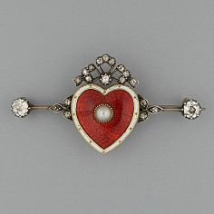 A red enamelled heart brooch The central motif with a pearl to the centre, white enamel surround and diamond-set scrolls above, flanked by smaller scrolls and diamond end stones, 4.0cm.