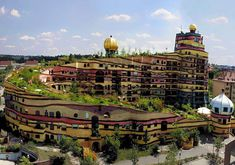 The whimsical Waldspirale is a residential building complex in Germany with an unconventional design that spirals upward to the green roof, which fosters several varities of bushes, flowers, and trees.  Architect: Friedensreich Hundertwasser  http://bit.ly/gb_ — con pick-a-pepper en Darmstadt, Germany.