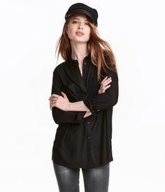 Svart. En rakt skuren skjorta i vävd kvalitet. Skjortan har smal turn down-krage och bröstfickor. Lång ärm som kan fästas upp med slejf och…