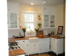 apron sink, white cabinets, glass door, hardwood floors. i like the shelves by window.