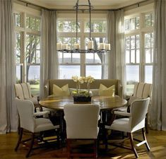 Gorgeous round dining table in front of a bay window with an amazing water view! Wonderful design by Hickman and Associates - round dining tables - monochromatic color scheme - casual dining room
