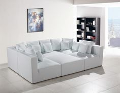 The 206 modern white leather sectional sofa exhibits an utmost level of comfort with its white bonded leather upholstery. It includes 3 1-seaters, 2-corner sofa, an ottoman and pillows, offering adequate seating and warmth for a cozier feel. This sectional can be arranged to blend with any home interior design.