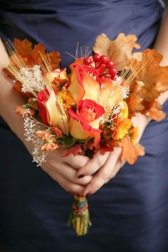 A Beautiful Autumn Bridesmaid's Bouquet Showcasing: Bi-Color Super Hot Pink/Yellow Circus Roses, Orange Button Mums, Golden Wheat, Red Holly Berries, White Riceflower, & Large Fall Maple Leaves... Very Cool Bouquet!××××