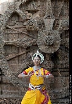 Odissi dancers strike pose re_enacts in front of iconic Sun Chariot in world heritage Sun temple complex in Konarak.