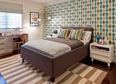 Fun boy's bedroom with Aimee Wilder Robots Wallpaper - Blue, brown queen headboard bed, Madeline Weinrib Platinum Buche Rug, white modern nightstands, stainless steel industrial desk, Cherner Side Chair and gray custom roman shades.