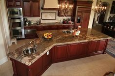 Crema Bordeaux Granite Countertops, cherry cabinets, pale beige floors (travertine?)