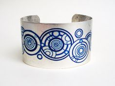 Adore -- and totally want. Doctor Who Blue Gallifreyan Symbols on Silver Cuff. $26.00, via Etsy.